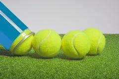 Concepto del tenis: las pelotas de tenis fuera de un envase mienten en arte verde Foto de archivo libre de regalías