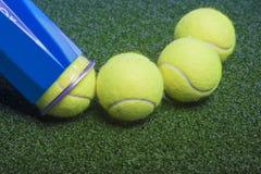 Concepto del tenis: las pelotas de tenis fuera de un envase mienten en gra verde Foto de archivo libre de regalías