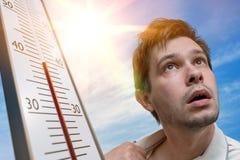 Concepto del tiempo caliente El hombre joven está sudando El termómetro está mostrando temperatura alta Sun en fondo Imagen de archivo libre de regalías