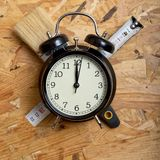Concepto del tiempo de DIY Herramientas que rodean un despertador negro foto de archivo libre de regalías