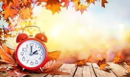 Concepto del tiempo del horario de verano - reloj y hojas Imágenes de archivo libres de regalías