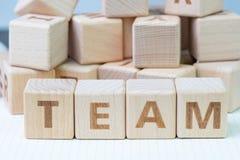 Concepto del trabajo en equipo, bloque de madera del cubo con las letras que forman la palabra EQUIPO en el cuaderno blanco del g imagenes de archivo