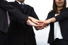 Concepto del trabajo en equipo del negocio con el amontonamiento de las manos del hombre de negocios y de empresarias Foto de archivo libre de regalías