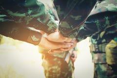 Concepto del trabajo en equipo: Grupo de proceso de Hands Together Cross del soldado Fotografía de archivo