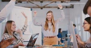 Concepto del trabajo en equipo La mujer de negocios caucásica sonriente feliz que lleva a empleados multiétnicos combina en la di almacen de metraje de vídeo