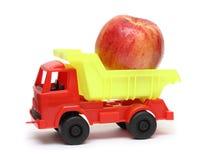 Concepto del transporte del alimento - camión del juguete con la manzana Fotos de archivo