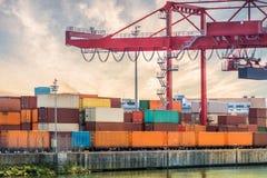 Concepto del transporte, del envío y de la logística Crane y muchos envases en puerto en la puesta del sol Imagen de archivo libre de regalías