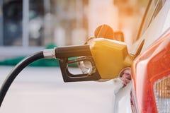 Concepto del transporte y de la propiedad - la gasolina de bombeo aprovisiona de combustible Imagen de archivo libre de regalías