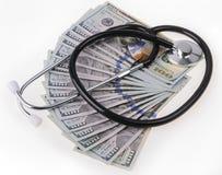 Concepto del tratamiento médico y del coste: estetoscopio que coloca en billetes de banco de los dólares de EE. UU. Fotografía de archivo libre de regalías