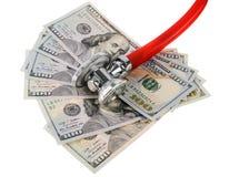 Concepto del tratamiento médico y del coste: estetoscopio que coloca en billetes de banco de los dólares de EE. UU. Imagen de archivo