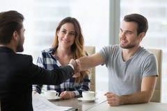 Concepto del trato de las propiedades inmobiliarias, agente inmobiliario feliz del apretón de manos de los clientes de los pares imagenes de archivo