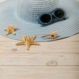 Concepto del verano de la playa Sombrero y gafas de sol femeninos azules en una luz Imagenes de archivo