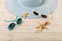 Concepto del verano de la playa Sombrero y gafas de sol femeninos azules en una luz Imágenes de archivo libres de regalías