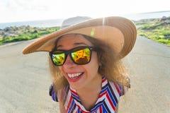Concepto del verano, del día de fiesta, del selfie y de las vacaciones - mujer joven que hace la cara divertida en el sombrero y  Foto de archivo
