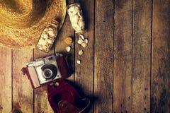 Concepto del verano o de las vacaciones Sombrero de paja con la cámara vieja del vintage Imagen de archivo libre de regalías