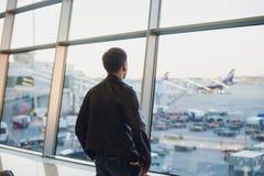 Concepto del viaje con el hombre joven en interior del aeropuerto con la opinión de la ciudad y un vuelo plano cerca fotografía de archivo