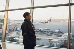Concepto del viaje con el hombre joven en interior del aeropuerto con la opinión de la ciudad y un vuelo plano cerca fotos de archivo
