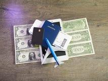 Concepto del viaje con la tableta, las tarjetas de crédito y los boletos del vuelo en la tabla oscura Foto de archivo libre de regalías