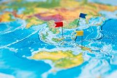 Concepto del viaje con los pasadores y el mapa del mundo de la bandera Foto de archivo libre de regalías