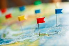Concepto del viaje con los pasadores y el mapa del mundo de la bandera Imagen de archivo libre de regalías