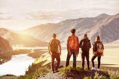 Concepto del viaje de cuatro de los amigos montañas de la puesta del sol imagen de archivo