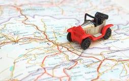 Concepto del viaje de la imagen, pequeño rojo, coche negro en mapa Imágenes de archivo libres de regalías
