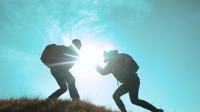 Concepto del viaje de negocios de la ayuda del trabajo en equipo dos caminantes hombre y escaladores de los turistas de la mujer  almacen de video