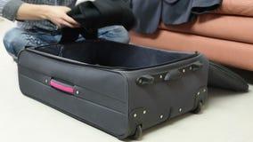 Concepto del viaje, del equipaje y de la gente - sirva la ropa del embalaje en bolso del viaje almacen de video