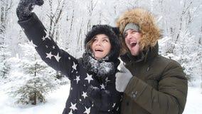 Concepto del viaje del invierno Pares jovenes felices que hacen la foto del selfie en smartphone al aire libre con el bosque de l metrajes