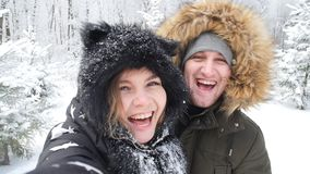 Concepto del viaje del invierno Pares jovenes felices que hacen la foto del selfie en smartphone al aire libre con el bosque de l almacen de metraje de vídeo