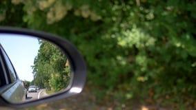 Concepto del viaje o del transporte del tráfico Retrovisor que refleja la línea de coches en el camino en almacen de metraje de vídeo