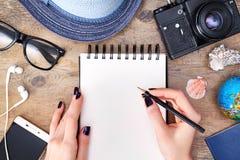 Concepto del viaje, planeamiento del viaje La mujer escribe en el cuaderno en fondo de madera fotografía de archivo