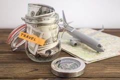 Concepto del viaje del presupuesto Ahorros del dinero del viaje en un tarro de cristal con los aviones del juguete en mapa del mu fotografía de archivo