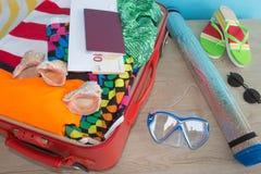 Concepto del viaje y de las vacaciones Abra el bolso del ` s del viajero con ropa, accesorios, los boletos y el pasaporte Fotos de archivo libres de regalías
