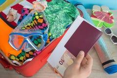 Concepto del viaje y de las vacaciones Abra el bolso del ` s del viajero con ropa, accesorios, los boletos y el pasaporte Fotografía de archivo