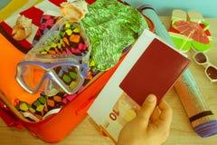 Concepto del viaje y de las vacaciones Abra el bolso del ` s del viajero con ropa, accesorios, los boletos y el pasaporte Imagen de archivo libre de regalías