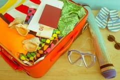 Concepto del viaje y de las vacaciones Abra el bolso del ` s del viajero con ropa, accesorios, los boletos y el pasaporte Foto de archivo libre de regalías