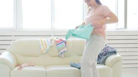 Concepto del viaje y de las vacaciones La mujer joven feliz está embalando la ropa colorida del verano en la maleta del equipaje  almacen de video