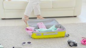 Concepto del viaje y de las vacaciones La mujer joven feliz est? embalando la ropa colorida del verano en la maleta del equipaje  almacen de video