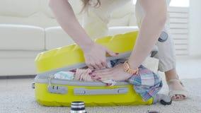Concepto del viaje y de las vacaciones La mujer joven feliz est? embalando la ropa colorida del verano en la maleta del equipaje  almacen de metraje de vídeo