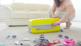 Concepto del viaje y de las vacaciones La mujer joven feliz est? embalando la ropa colorida del verano en la maleta del equipaje  metrajes