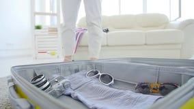 Concepto del viaje y de las vacaciones Ropa y materia que embalan en la maleta abierta grande almacen de video