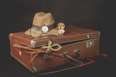Concepto del viaje y del advanture Maleta marrón del vintage con la llave del reloj, del sombrero del defora, del bullwhip, del c Imagen de archivo libre de regalías