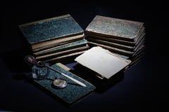 Concepto del vintage con los libros viejos, los papeles, la pluma de la tinta y el tintero Fotografía de archivo