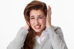 Concepto del zumbido, mujer nerviosa 20s que sufre de los dientes de pulido del dolor de cabeza foto de archivo libre de regalías