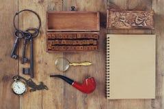 Concepto detective Herramientas del detective privado: vidrio de la lupa, viejas llaves, tubo que fuma, cuaderno Visión superior  Foto de archivo
