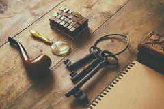Concepto detective Herramientas del detective privado: vidrio de la lupa, viejas llaves, tubo que fuma, cuaderno Visión superior  Imagen de archivo libre de regalías