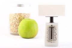Concepto dietético: escamas del balance, de la manzana y de la avena Imágenes de archivo libres de regalías