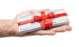 Concepto, dinero como regalo, triunfo o prima La mano del ` s del hombre toma o da la pila de 100 billetes de dólar atados con la Fotografía de archivo