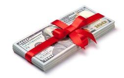 Concepto, dinero como regalo, triunfo o prima La pila de 100 billetes de dólar se ata con la cinta roja con el arco Aislado en bl Fotografía de archivo